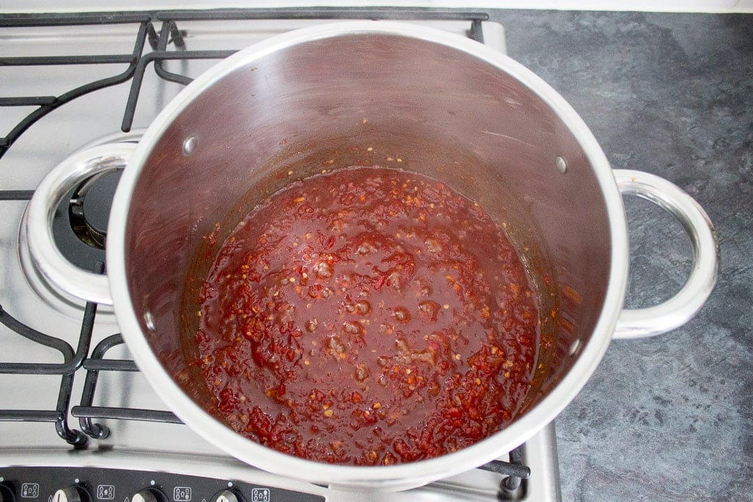 reducing sweet chilli jam in a large pot on the hob