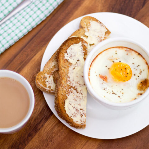 A small white bowl of baked eggs, ham and tomatoes on a white plate with toast and butter. Set on a deep wooden backdrop with a cup of tea, a green checked tea towel and a spoon.