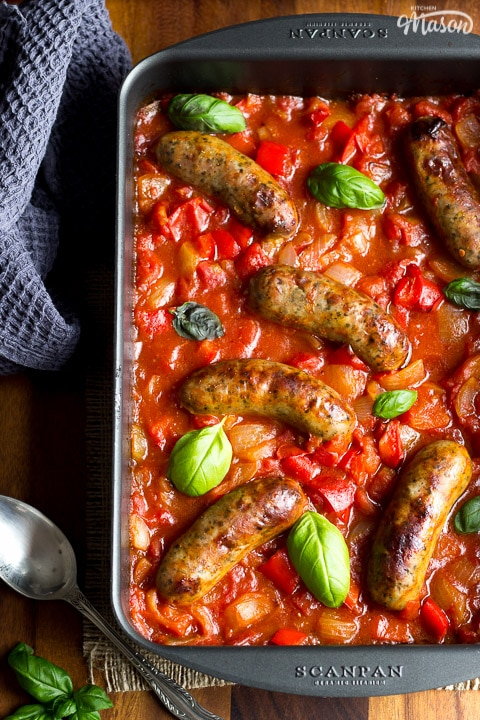 easy sausage casserole in a roasting dish topped with fresh basil leaves