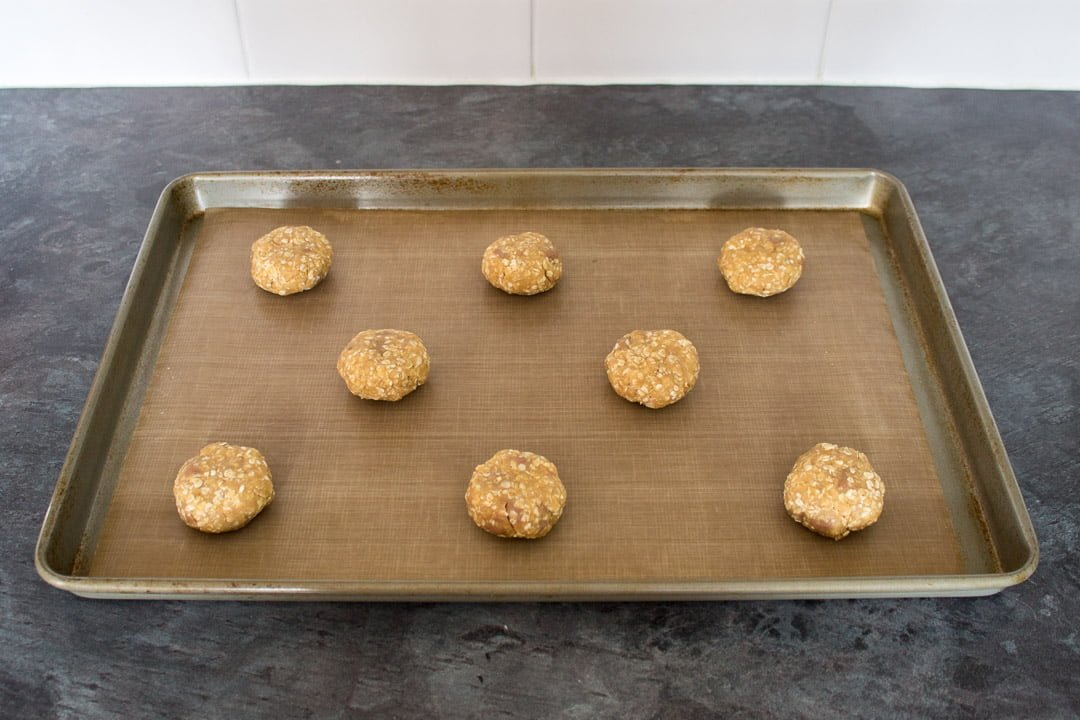 Chocolate hobnobs cookie dough balls on a lined baking tray