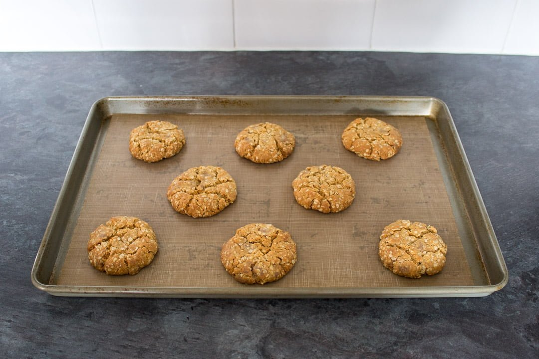 Baked chocolate hobnobs on a lined baking tray