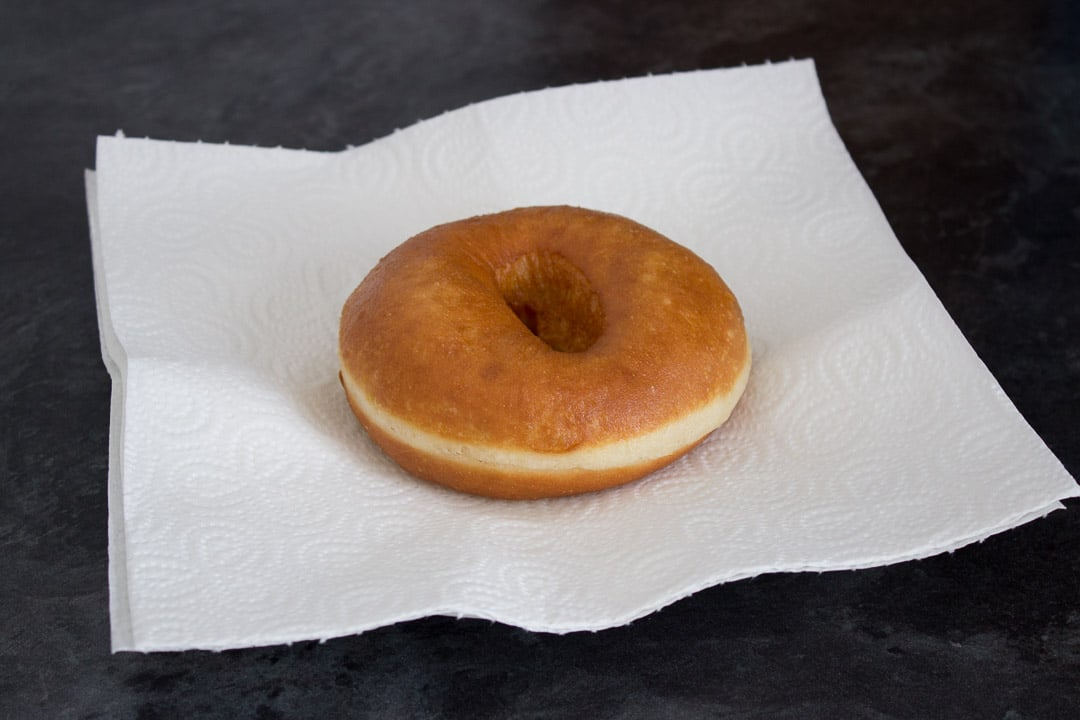 freshly fried homemade doughnut on a piece of kitchen roll