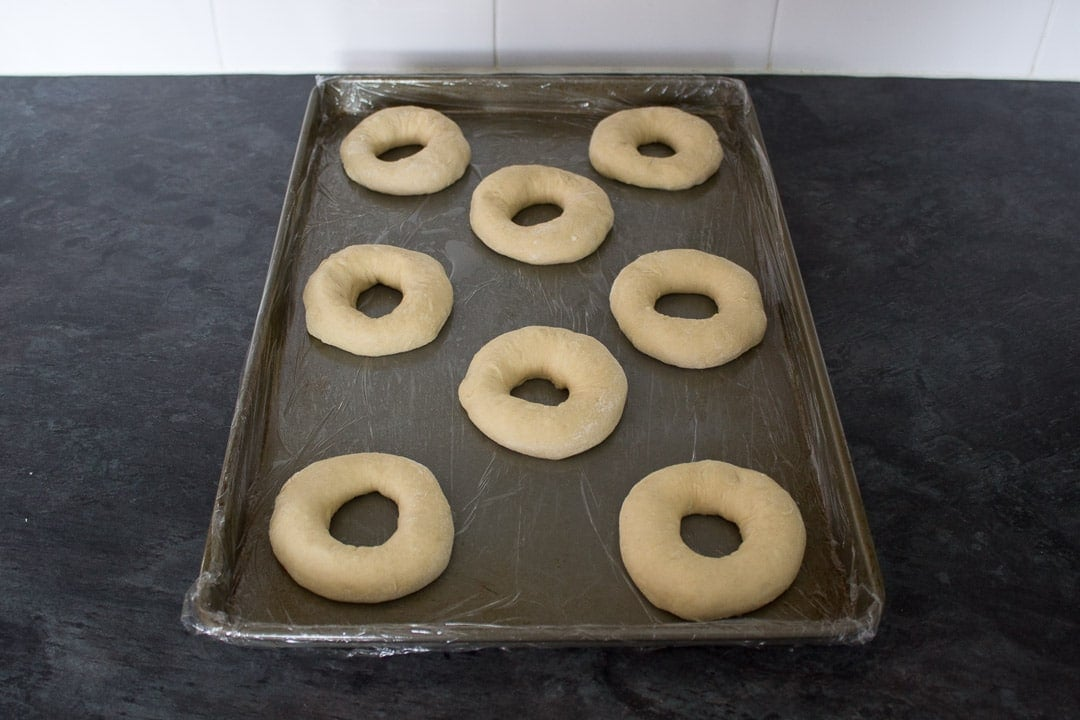 unbaked homemade doughnut rings on a baking tray