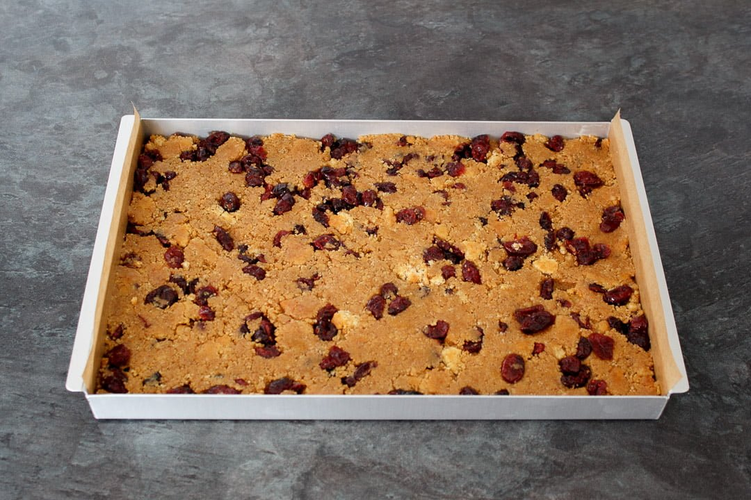 cranberry white chocolate tiffin mixture pressed into a lined baking tray