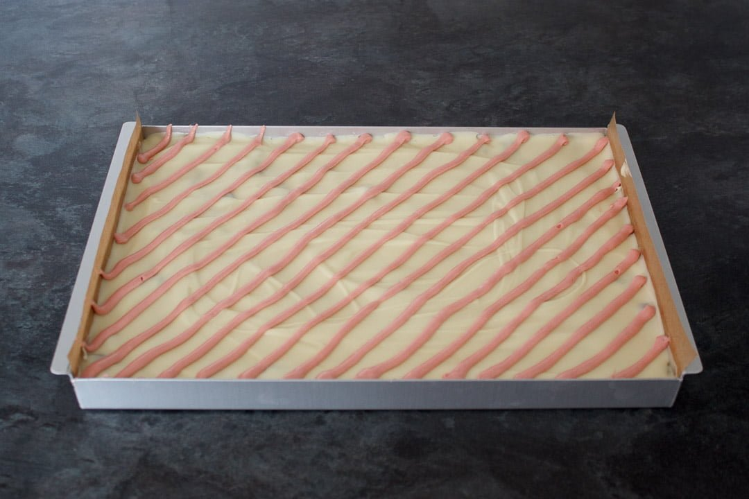 cranberry white chocolate tiffin with melted chocolate poured over the top and pink chocolate lines piped over for decoration