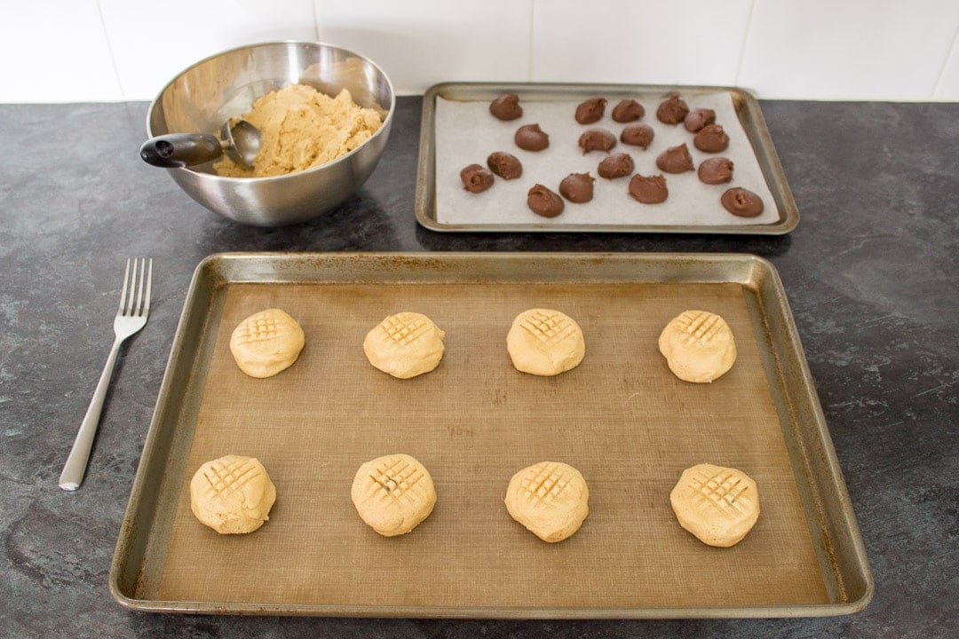 frozen nutella blobs wrapped in peanut butter cookie dough, spaced out on a lined baking tray