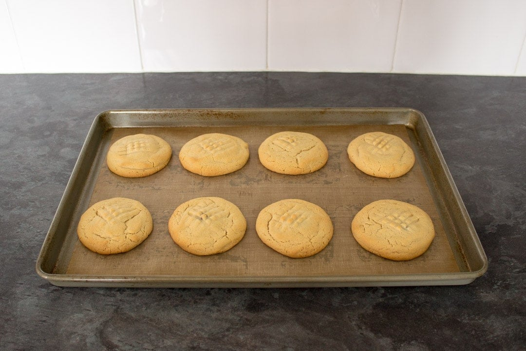 baked nutella stuffed peanut butter cookies on a lined baking tray