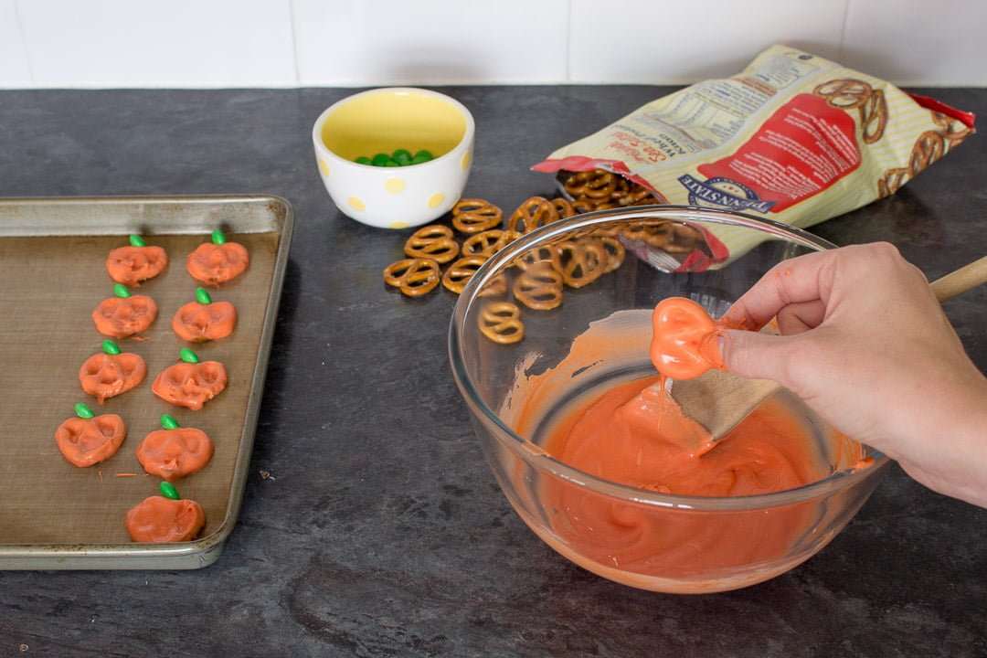 Pretzels being dipped into orange coloured white chocolate then topped with a green M&M and placed onto a baking tray