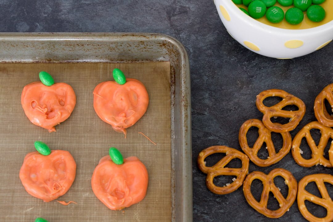 pumpkin chocolate covered pretzels setting on a lined baking tray
