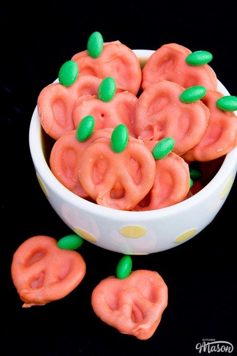 Pumpkin chocolate covered pretzels in a white bowl