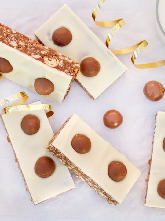 Malteser Tiffin Bars, a glass of milk and gold curling ribbon lay on a table.