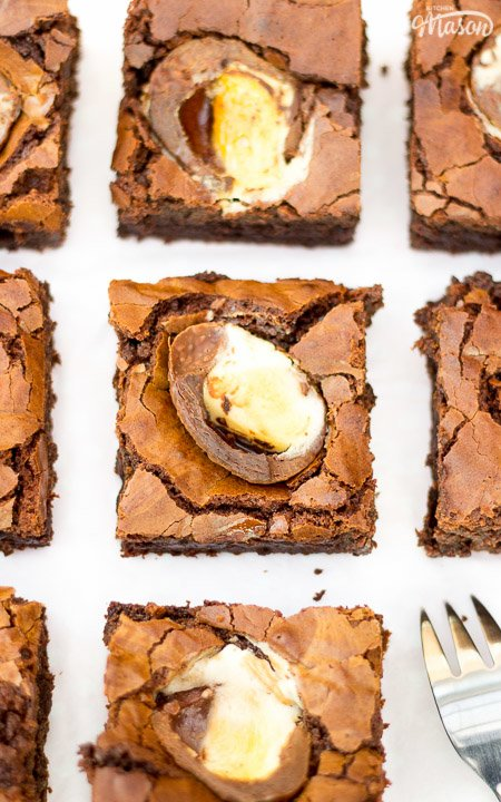 Creme egg brownies cut into squares on a sheet of baking paper with a fork