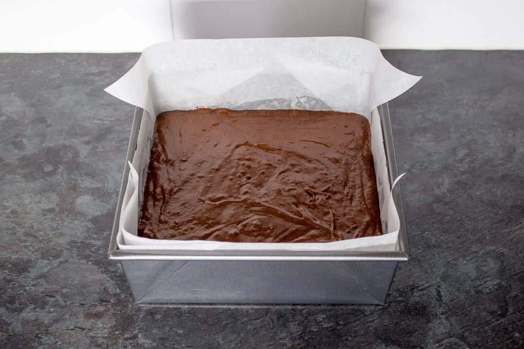 creme egg brownie batter in a lined, square baking tin