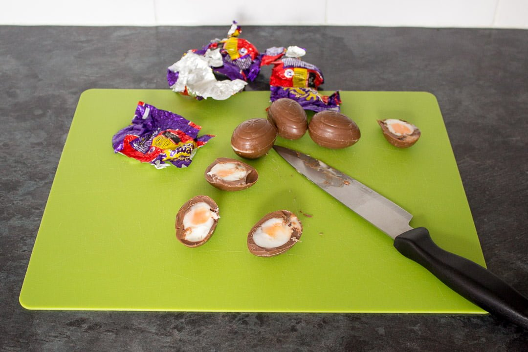 creme eggs sliced in half on a chopping board, with a sharp knife.