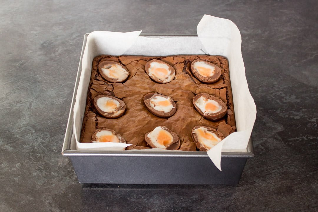 part cooked brownies with halved creme eggs pushed slightly into the top