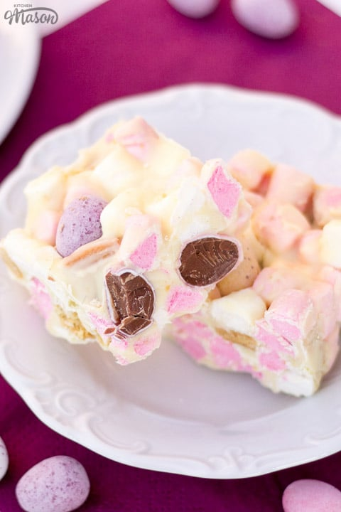 Mini Egg rocky road bars on a white plate with Mini Eggs scattered around.