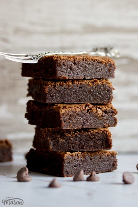 fudgy brownies in a stack with a fork on top