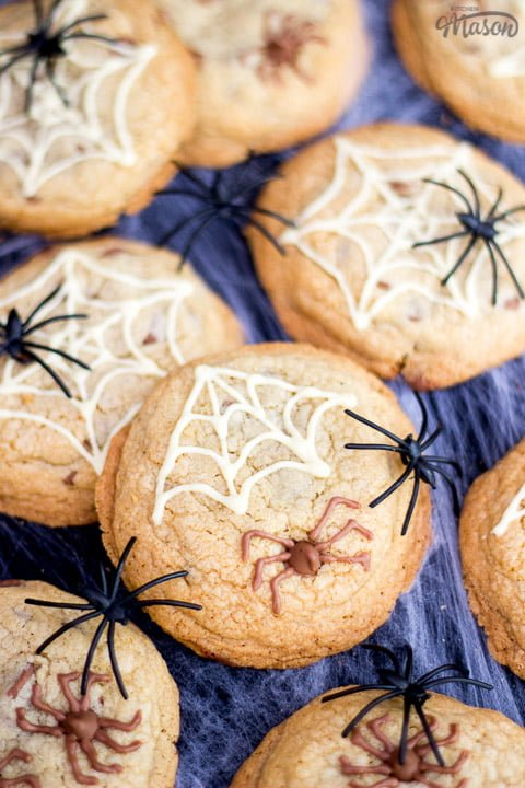 chocolate chip halloween spider cookies on a spider web with black plastic spiders