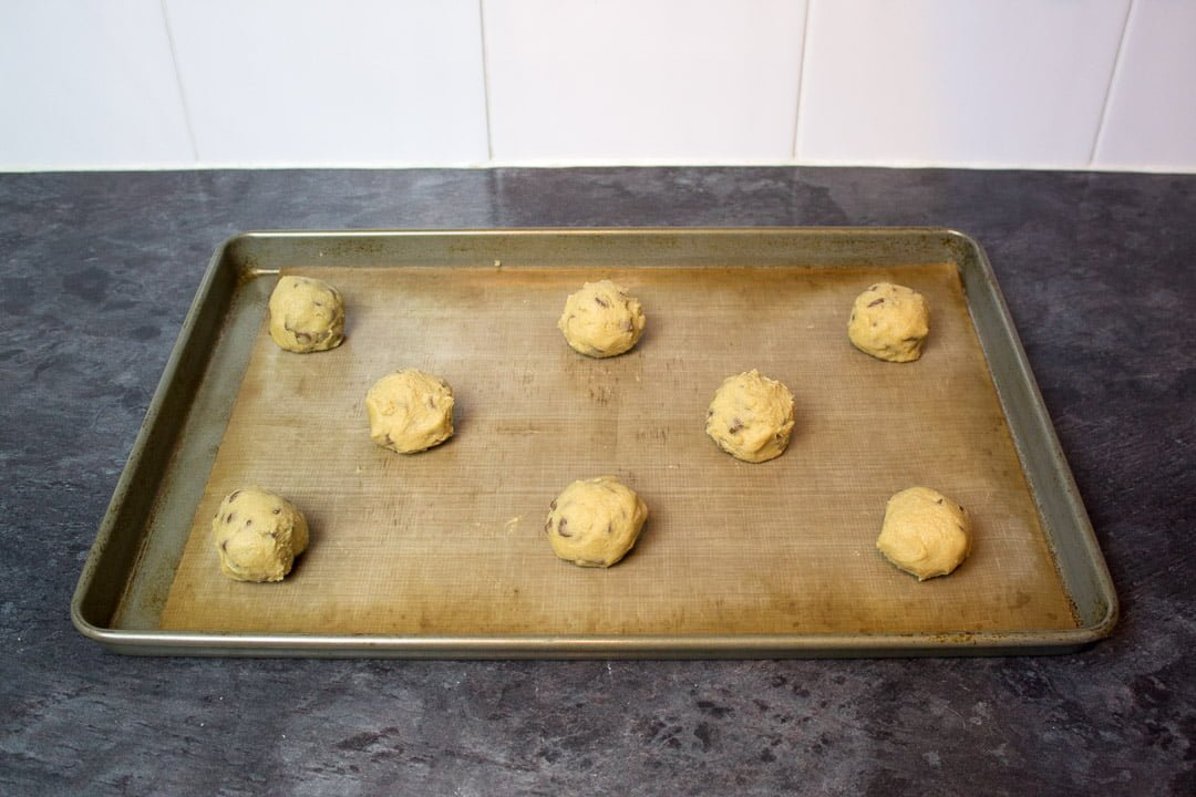 spider cookie dough balls on a lined baking sheet
