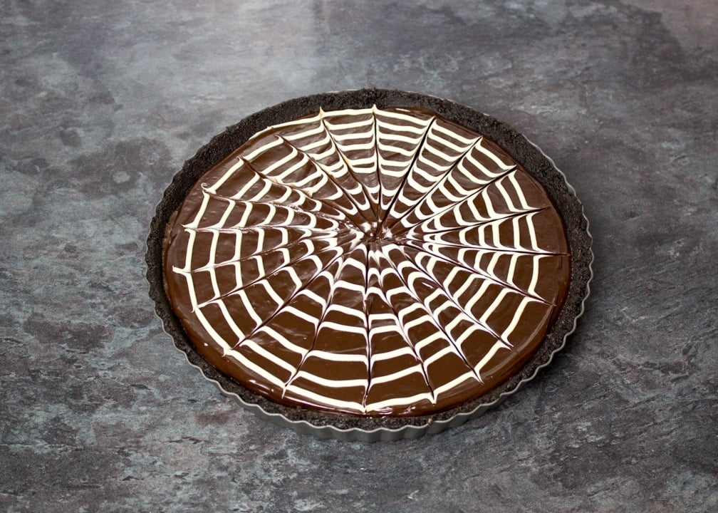 White chocolate spider web pattern skewered on top of a chocolate tart