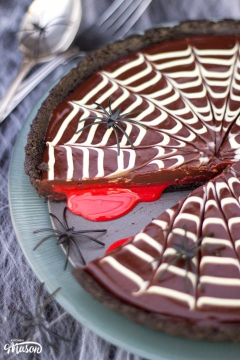 Halloween Dessert | No Bake Bloody Spider Web Chocolate Tart on a plate with plastic spiders