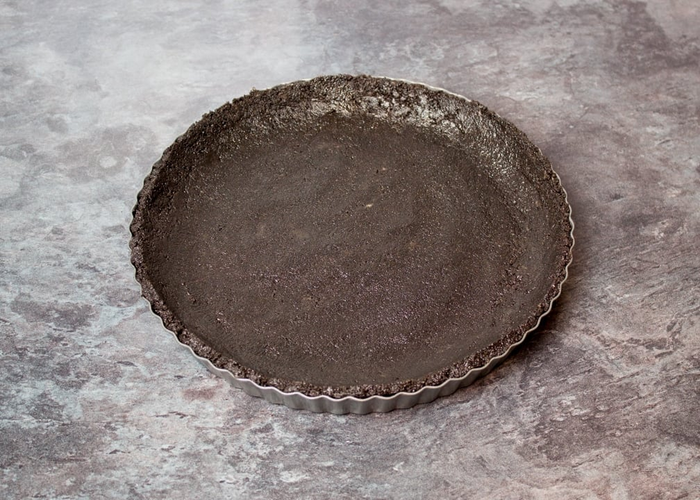 Oreo biscuit crumbs pressed into a fluted tin