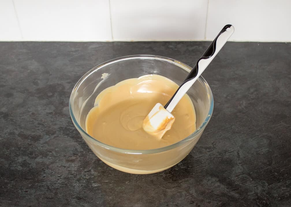 Melted white chocolate and biscoff in a glass bowl