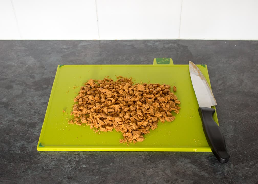 Chopped Biscoff biscuits on a green chopping board
