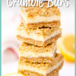 4 lemon cream crumble bars in a stack with a sliced lemon in the background