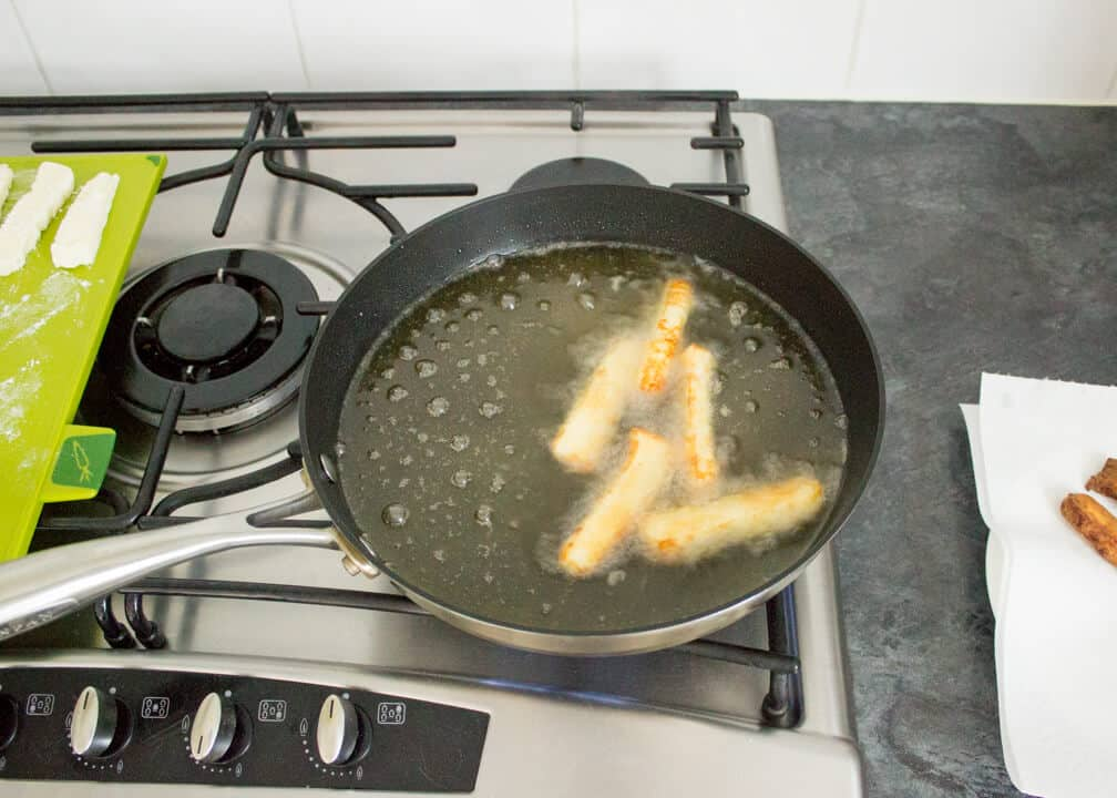 Halloumi Fries in a frying pan filled with hot oil