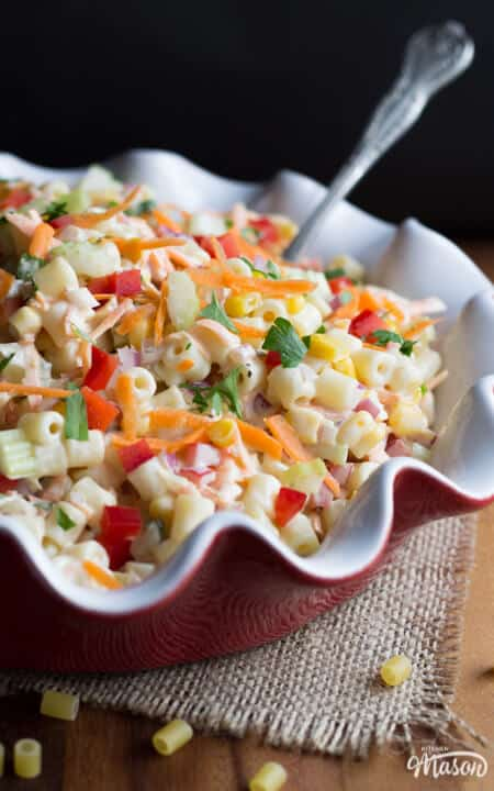 Rainbow pasta salad in a red and white ceramic dish set over a wooden worktop.