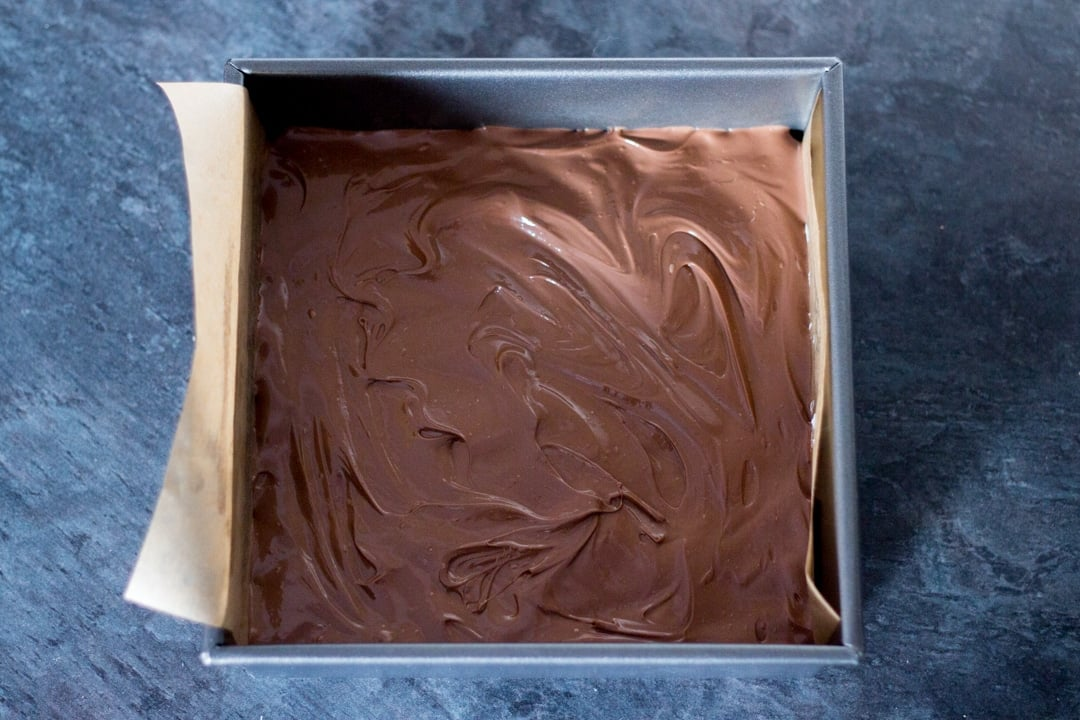 melted chocolate smoothed over a rice krispie marshmallow mixture in a baking tin
