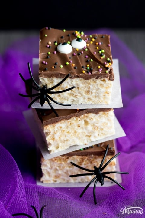 Rice Krispie Halloween Treats in a stack with fake black spiders crawling up
