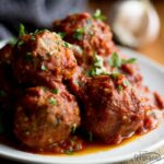 Slow Cooker Meatballs on a plate with parsley scattered on top