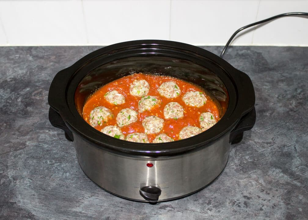 Uncooked meatballs in a sauce in a slow cooker