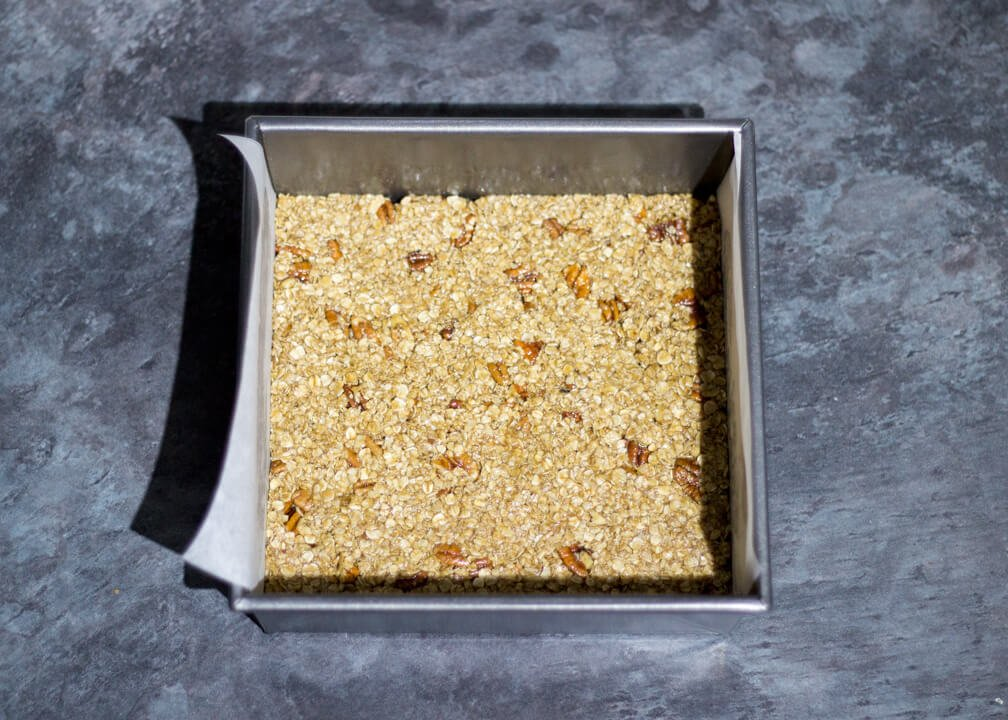 Flapjack Recipe: maple pecan flapjack mixture pressed into a lined square baking tin