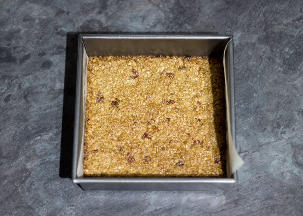 Flapjack Recipe: baked maple pecan flapjack in a lined square baking tin