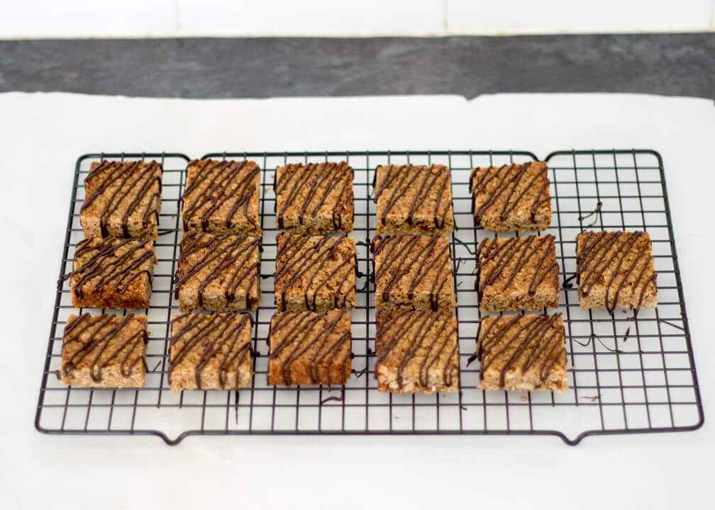 Flapjack Recipe: maple pecan flapjacks on a cooling rack drizzled in chocolate