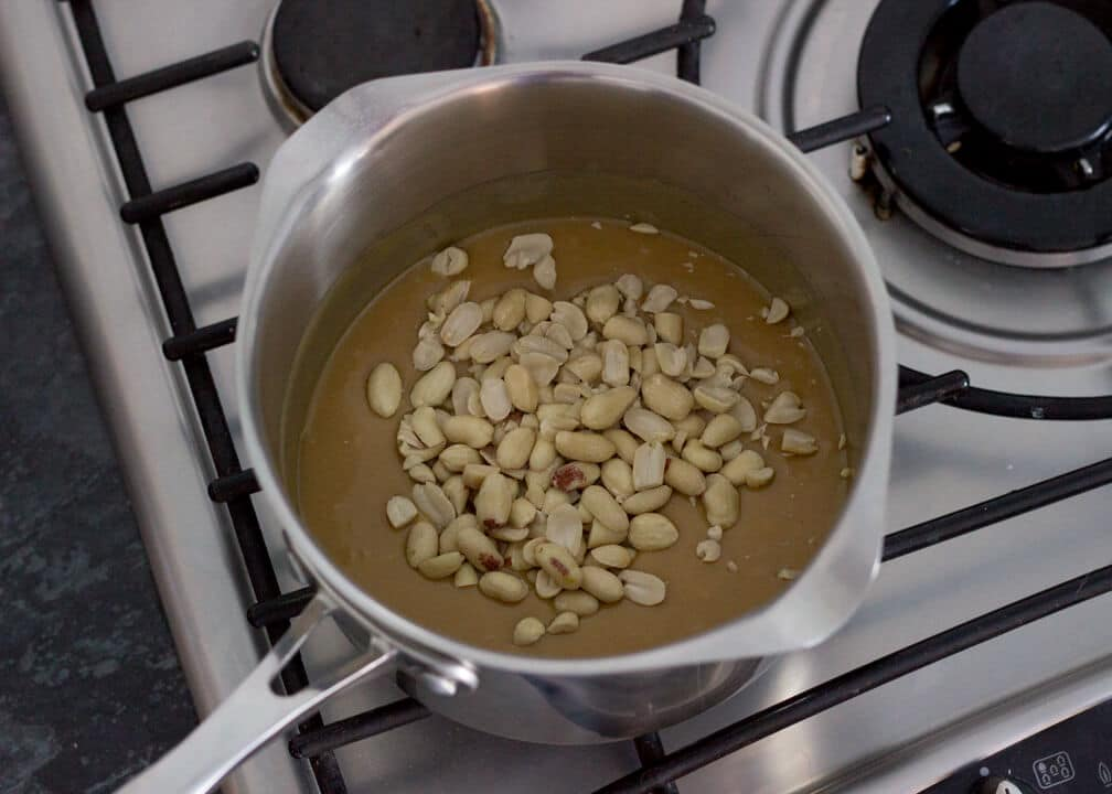 Snickers Millionaire Shortbread - boiled caramel in a saucepan with peanuts