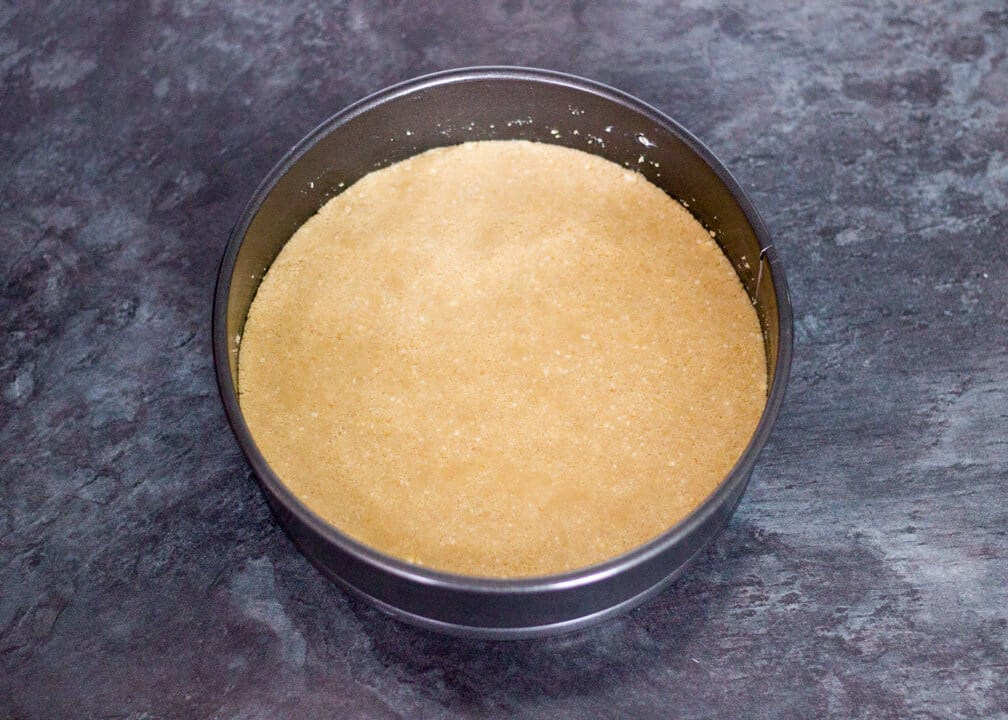 Baked cheesecake biscuit crumb base in a tin