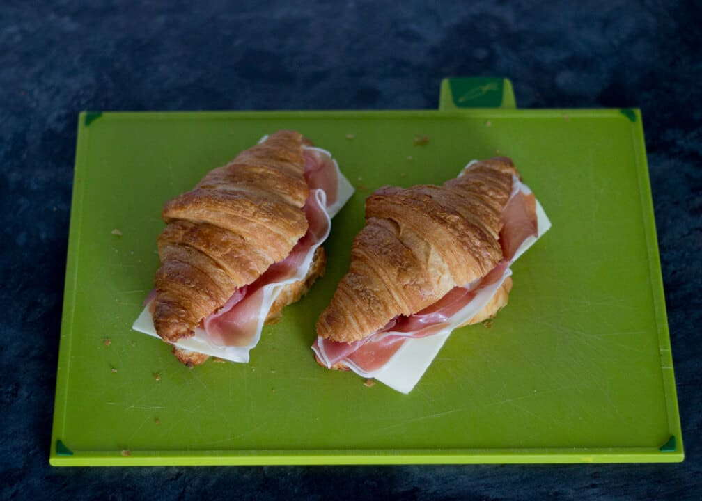 Croissant Sandwich with Prosciutto & Gouda on a Chopping Board