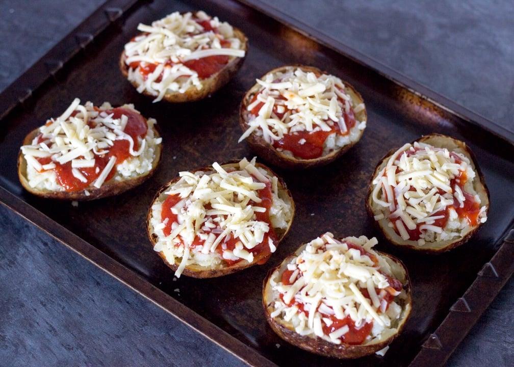 Pizza loaded potato skins on a baking tray