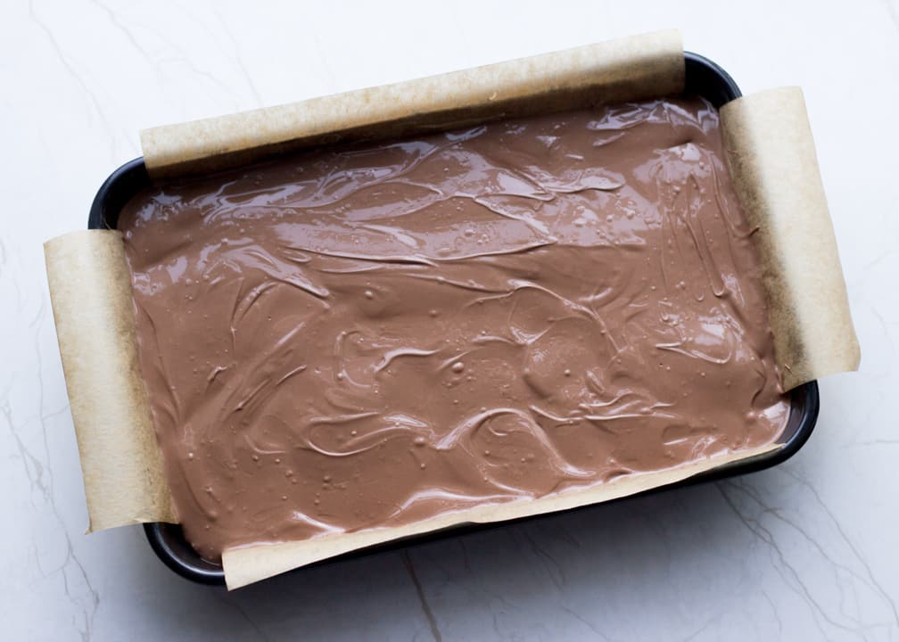 Chocolate Orange Caramel Shortbread: melted chocolate smoothed over the caramel layer in the baking tray