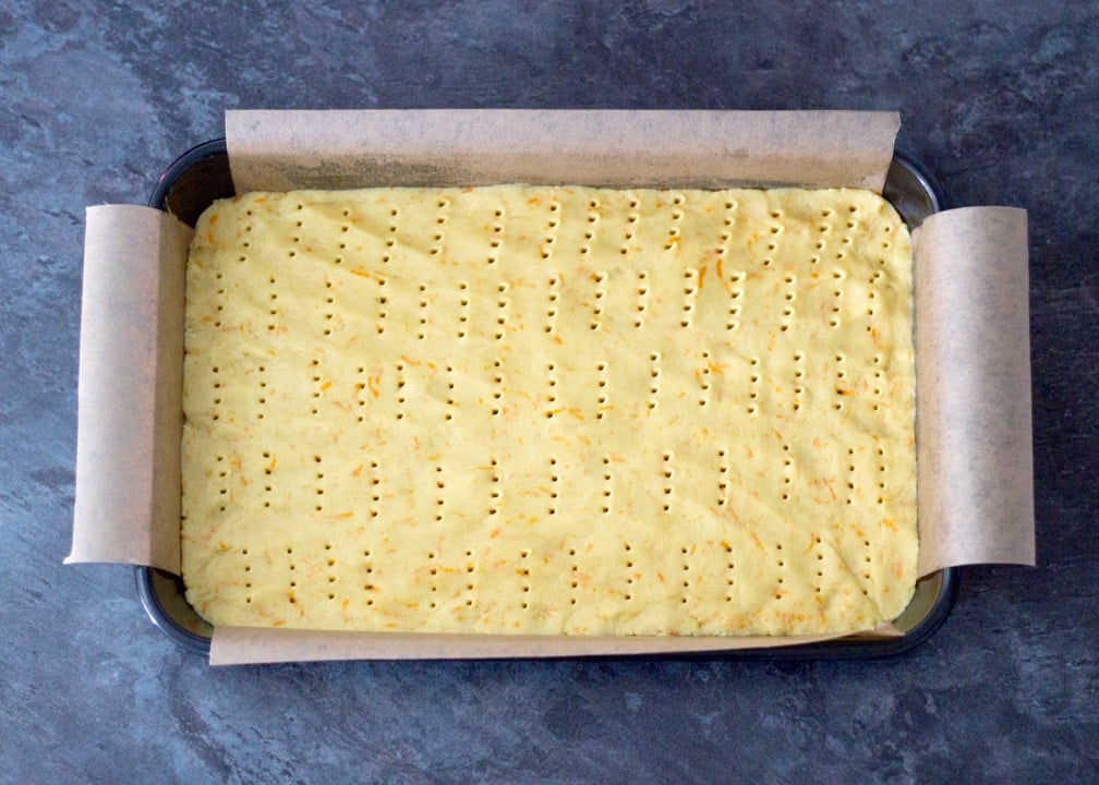 Chocolate Orange Caramel Shortbread: the biscuits base dough pressed into a baking tray and pricked with a fork