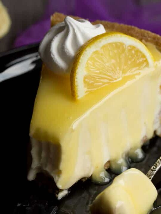 Lemon Cheesecake Recipe: slice of lemon cheesecake on a plate topped with a meringue nest and lemon slice