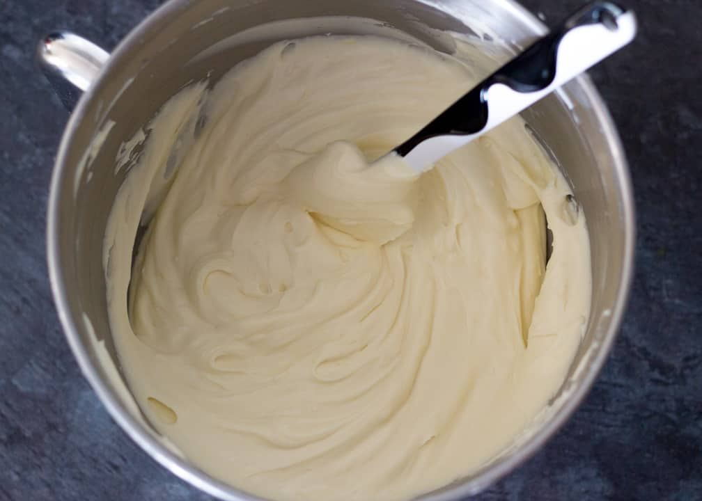 Lemon Cheesecake Recipe: beaten cream cheese, sugar and lemon curd in a stand mixer bowl with whipped double cream folded in