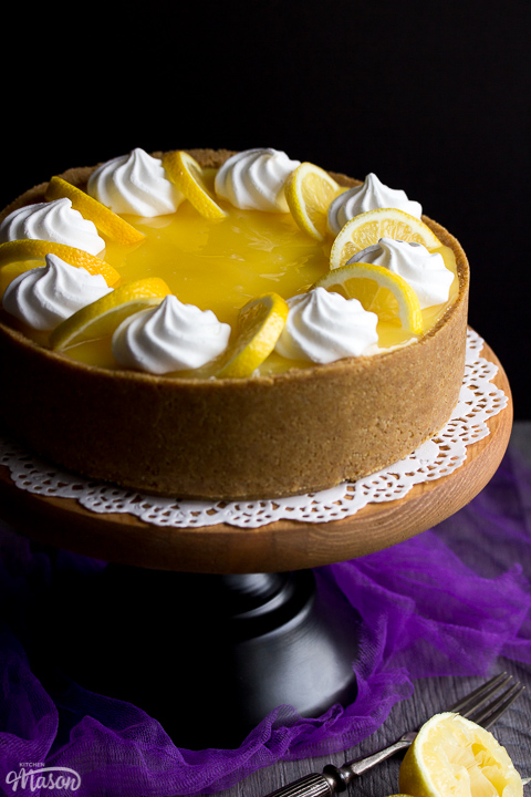 A whole no bake lemon cheesecake on a cake stand set over purple mesh fabric. Topped with meringue nests and lemon slices.
