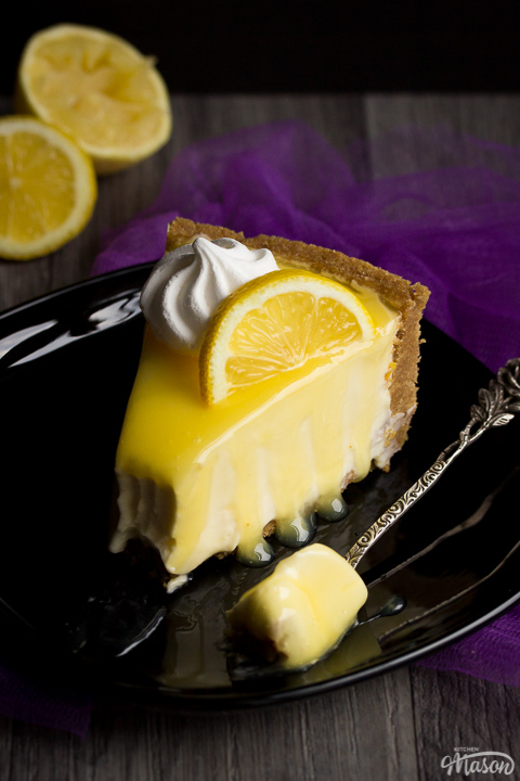A slice of lemon cheesecake on a black plate topped with a meringue nest and lemon slice