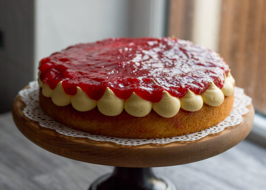 Sponge cake with custard icing piped on top in blobs topped with rhubarb jam