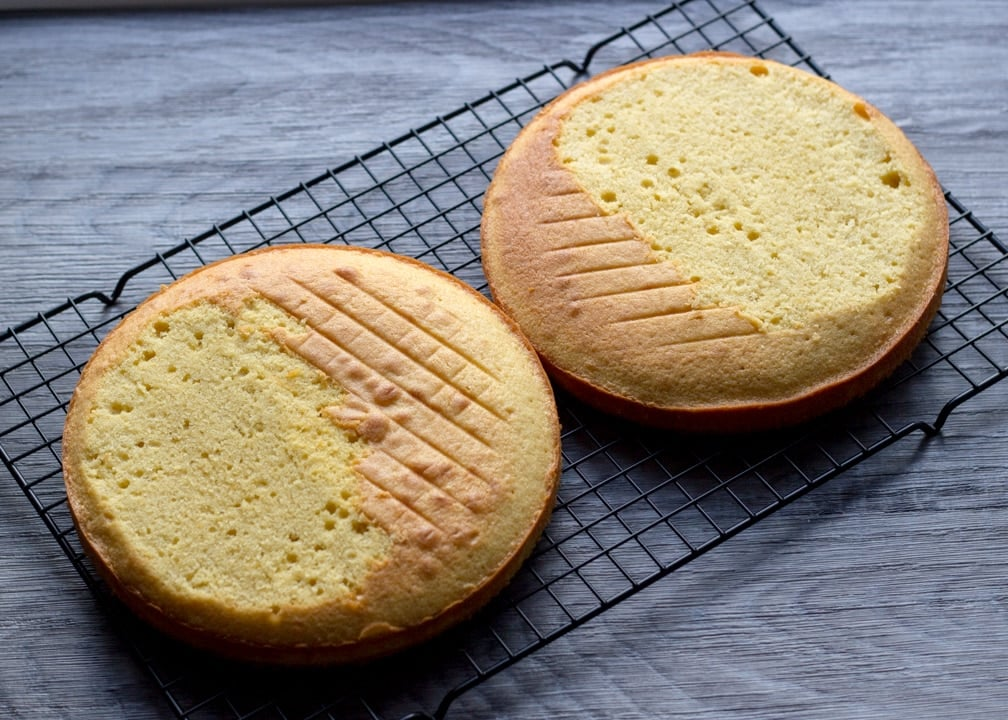 Two sponge cakes on a cooling rack with the domed parts leveled off